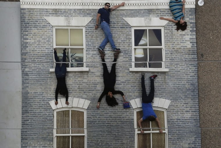 Visitors enjoy an art installation by Argentinan artist Leandro Erlich in London, Tuesday, June 25, 2013. Internationally known for his captivating, three-dimensional visual illusions, Argentine artist Leandro Erlich has been commissioned to create a new installation in Dalston London. Resembling a theatre set, the detailed facade of a Victorian terraced house, recalling those that once stood on the street, lies horizontally on the ground with mirrors positioned overhead. The reflections of visitors give the impression they are standing on, suspended from, or scaling the building.(AP Photo/Frank Augstein)