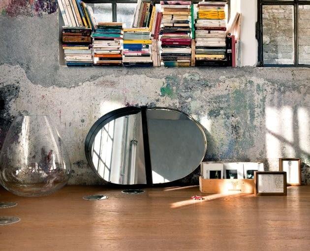 Przemysłowa poezja: zachowane fabryczne okna tworzą z freskiem spracowanych ścian malarską kompozycję, którą gospodarz uzupełnia dawką codziennego piękna: książkami, lustrem z antykwariatu, kolekcją rodzinnych zdjęć czy szklaną wazą.