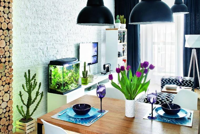 FABRYKA I NATURA. Industrialne elementy wystroju - lampy (Nowodvorski), reflektorki na szynie (Aquaform) oraz ceglana okładzina ściany - nie wydają się tak surowe w towarzystwie dębowych desek na podłodze (SolidPlus) i podświetlonego taśmą LED panela z krążków drewna (Stegu). Dużo życia wprowadza również akwarium.