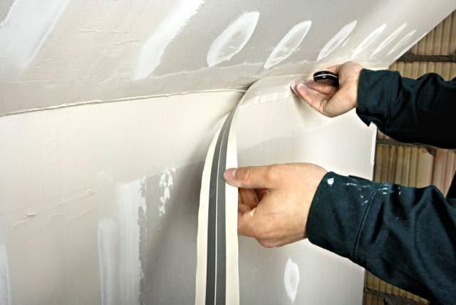Wklejanie taśmy papierowej z wkładką metalową w miejscu połączenia obudowy skosu i ściany kolankowej