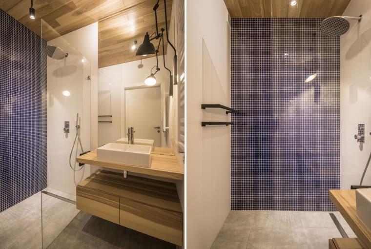 Zaglądamy do łazienki. Tu wzrok wędruje w górę na drewniany sufit, a następnie na ścianę pod prysznicem z granatowej mozaiki. Efekt? Z umiarem, a jednak elegancko.