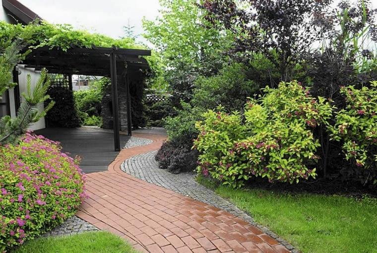 PRZY TARASIE znajduje się zróżnicowana nawierzchnia z kostki granitowej i klinkieru, która prowadzi do tylnej części ogrodu.