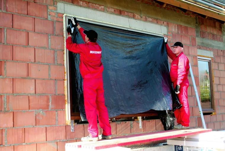 В двухслойных стенах перед установкой утеплителя обычно уже устанавливаются окна, которые следует тщательно закрыть.