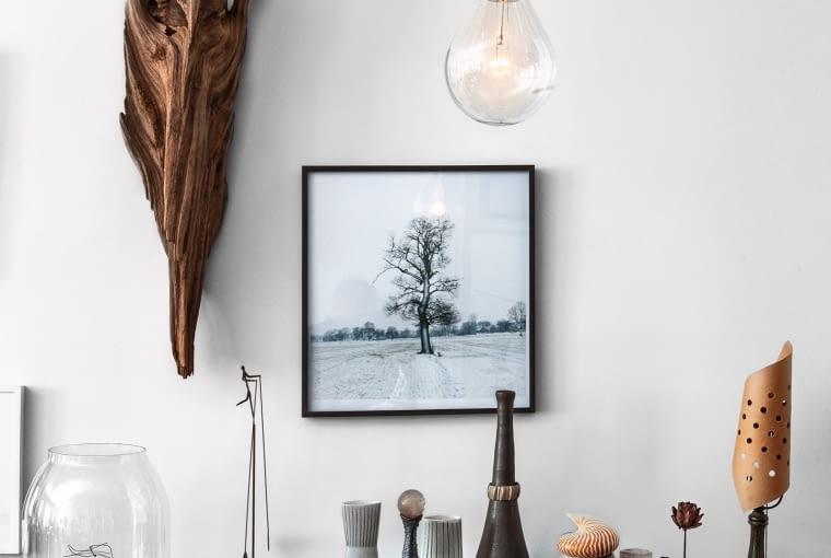 Dzieło sztuki i dzieło natury: obok fotografii Dietmara Busse wisi konar znaleziony w zatoce. Na stoliku lampka francuskiego designera Jeana Prouvé.