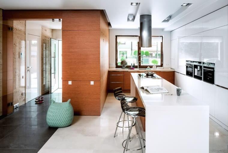PRACA W CENTRUM. Wyspę z długim blatem, umieszczoną na środku kuchni, z trzech stron otacza zabudowa w kształcie litery U. Ułatwia to pracę - łatwo sięgać do szafek i urządzeń zamontowanych przy ścianach.