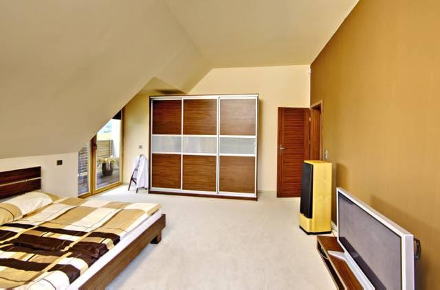 Widok na główną sypialnię na poddaszu, do której przylega duży balkon oraz taras nad wiatą
