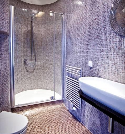 Kabina prysznicowa na opak. Prysznic ulokowany w półokrągłej wnęce, nadaje niewielkiemu wnętrzu oryginalny charakter