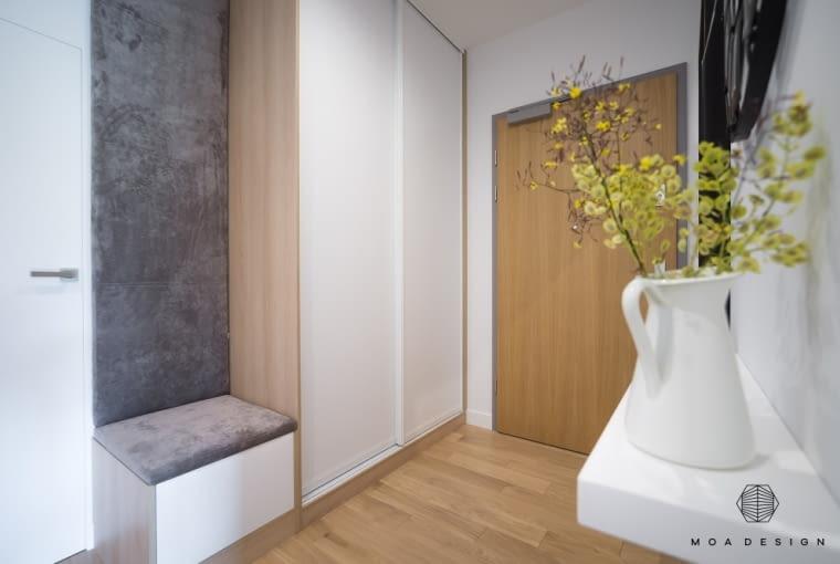 Przy drzwiach wejściowych jest miękkie siedzisko i duża, pojemna szafa.