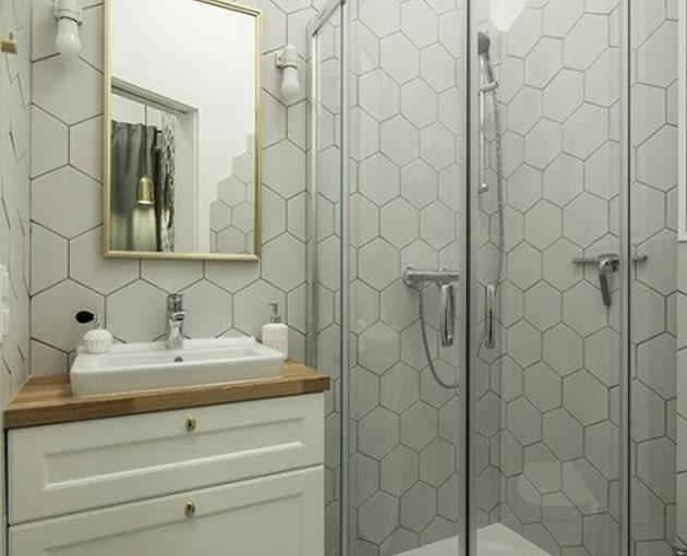 W łazience jest kabina prysznicowa z zaokrąglonymi kantami.