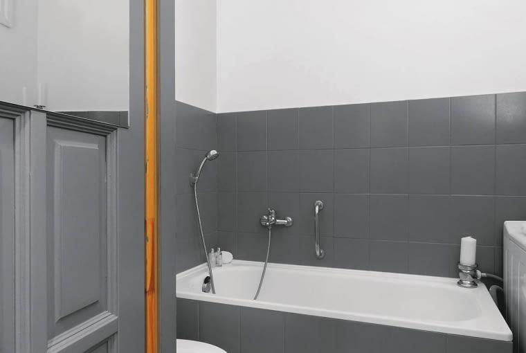 PO ZMIANIE. Drzwi, przedtem drewniane, przestały pasować do nowej kolorystyki łazienki. Ten problem również pomogły rozwiązać wałek i farba, tym razem przeznaczona do drewna. Jej odcień został idealnie dobrany do barwy przemalowanych płytek.