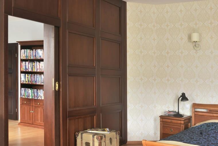 DOM. Sypialnię od biblioteki oddziela pokryta drewnianą boazerią ściana, w której zamontowano przesuwane drzwi (również drewniane).