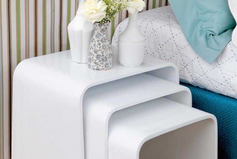Po drugiej stronie łóżka pojawiły się nowoczesne stoliki wsuwane jeden pod drugi. Taki zestaw zajmuje tyle samo miejsca co pojedynczy mebel, awrazie potrzeby zapewnia dodatkowy blat, np. na postawienie talerza ikubka (pomysł dla osób lubiących jeść włóżku!). Są bardzo lekkie, wkażdej chwili można je więc przenieść do salonu, gdy przyjdzie więcej gości.