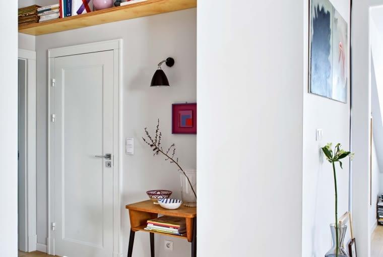Duma kolekcji, maleńki obraz abstrakcjonisty Henryka Stażewskiego, zawisł na ścianie w korytarzu łączącym salon z sypialnią. Nad drzwiami łazienkowymi zamocowano półkę na albumy. Na podłodze - chodniczki w geometryczne wzory (marki Pappelina).