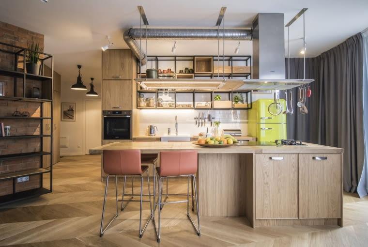 Oprócz podłogi z wzorem jodełki francuskiej o przytulności wnętrza decyduje również drewno na blatach i na frontach szafek. Z kolei industrialny charakter wnętrza podkreśla stalowy wyciąg z odsłoniętym orurowaniem, retro lodówka SMEG w kolorze soczystej limonki, a także widoczne w korytarzu przemysłowe lampy.