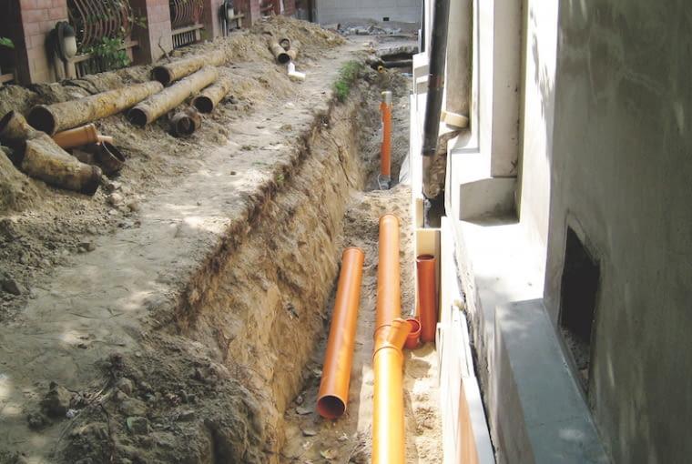 Wykonanie wokół domu drenażu opaskowego zabezpieczy fundamenty przed zawilgoceniem. Zgromadzoną w nim wodę trzeba odprowadzić w odpowiednie miejsce