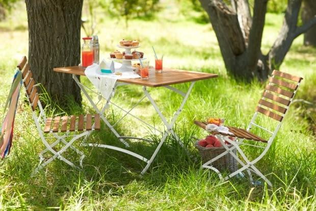 Składny stół z blatem z drewna akacjowego, na białym metalowym stelażu. Wymiary: 120 x 75 cm. Do stołu można dokupić krzesła w podobnym stylu. Wymiary: 120 x 75 cm. Tchibo, stół 650 zł., krzesło 300 zł.
