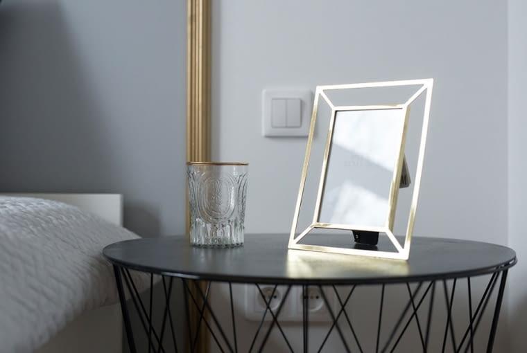 Złocona ramka na zdjęcia na metalowym stoliku o fantazyjnej podstawie.