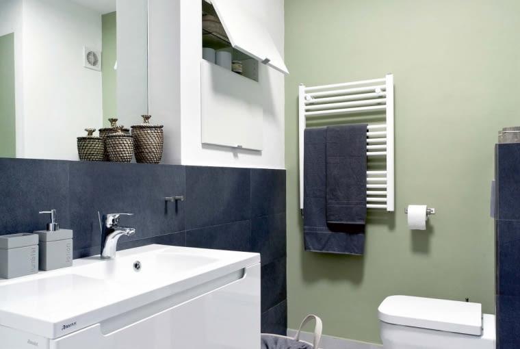Po remoncie. W łazience dominuje czerń i biel. Ten kolorystyczny 'dwugłos' został przełamany oliwkowym odcieniem zieleni, na który pomalowano niektóre ściany bądź ich fragmenty. Duża umywalka jest osadzona na szafce z pojemną szufladą. Podwieszony sedes zainstalowano na ściance wydzielającej niewielki schowek gospodarczy.