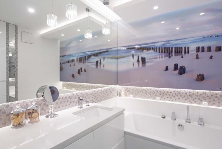 Łazienka z wanną to królestwo Julity i Oliwki. Wnętrze optycznie powiększa fototapeta i duże lustro. W szafce pod umywalką (tak jak większość mebli zrobionej na wymiar w firmie Kurosz Design) ukryto pralkę.