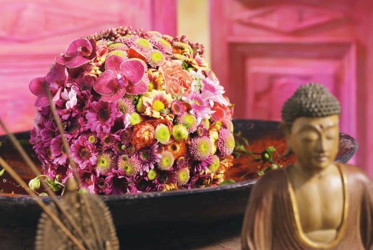 Orientalne kompozycje kwiatowe. W kulę z mokrej gąbki florystycznej powbijano ściśle główki chryzantem, nieśmiertelników, dalii, cynii, róż i falenopsisów