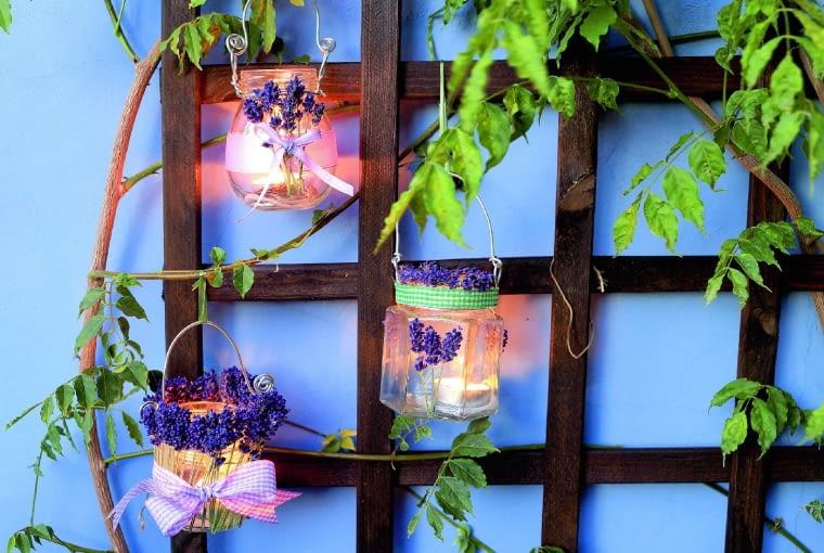 Zwykłe słoiki ozdobione wstążkami i kwiatkami lawendy, zawieszone na balkonowej kratce stworzyły świetlistą ściankę.