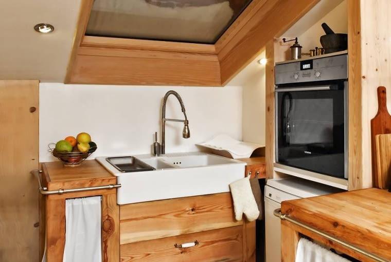 Kuchnie. Zlewozmywak zainstalowano pod oknem połaciowym, przez które w ciągu dnia wpada dużo naturalnego światła. Po zapadnięciu zmroku kuchnię oświetlają oczka ledowe zamontowane po bokach okna.