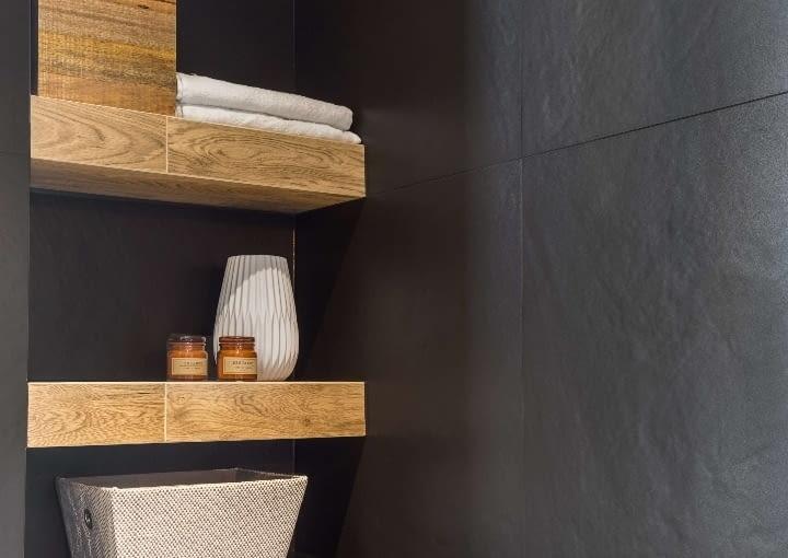 Płytki o strukturze drewna tworzą ciekawy kontrast z chropowatą powierzchnią grafitowych kafli i świetnie spisują się w roli półek we wnęce.