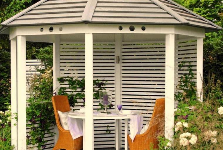 Wygodnie umeblowana drewniana altana - romantyczna ogrodowa kryjówka na upalne lato.