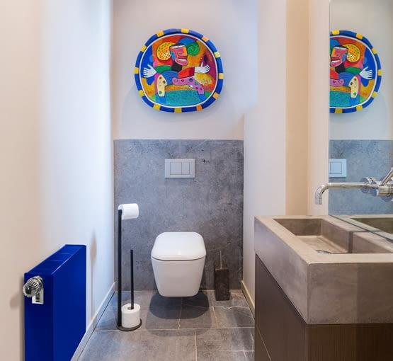 Najmocniejszymi akcentami kolorystycznymi w tej łazience są grzejnik (marki Purmo) i barwna ozdoba ścienna. Wprowadzone w tym sposób kolory to nietypowe rozwiązanie, ale zarazem bardzo trafione.