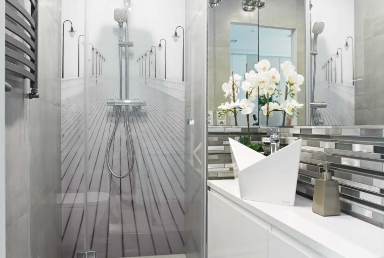Na ścianie fototapeta przedstawiająca molo, na blacie łódeczka (czyli umywalka firmy Marmorin). Całą szerokość drugiej łazienki zajmuje kabina prysznicowa zamykana szklanymi drzwiami.