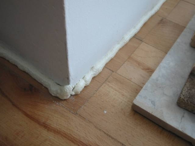 Grubszy warkocz piany naniosłem na styk podłogi i ściany. Właśnie rośnie. Po prawej stronie na podłodze leży kawałek płyty marmurowej, która będzie dociskać listwę do ściany