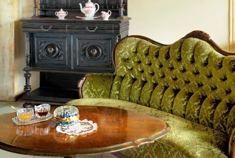 Przy kanapie i fotelach stał stolik fornirowany drewnem orzechowym, wsparty na toczonej podporze zakończonej trzema fantazyjnie wygiętymi nóżkami.