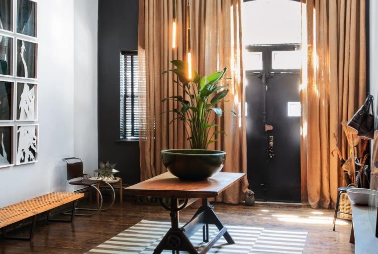 Dzięki długim zasłonom hol sprawia wrażenie przytulniejszego. Industrialny stół właściciel znalazł w piwnicy, wystarczyło go tylko oczyścić. Pod ścianą ławka George'a Nelsona i krzesło Marcela Breuera.