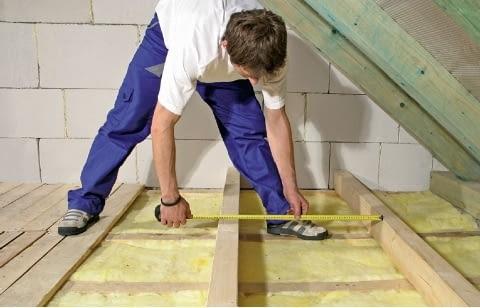 Układanie wełny mineralnej na stropie drewnianym - następnie rozmieszcza się belki. Ich rozstaw nie powinien przekraczać 60 cm, dzięki czemu będzie można wykonać podłogę z desek lub płyt drewnopochodnych (wiórowych lub OSB)