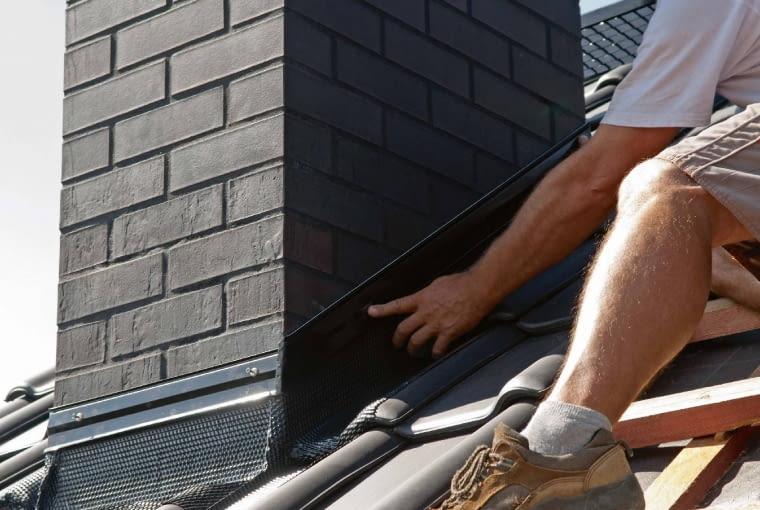 Wystającą nieco ponad łaty membranę dachową (lub papę układaną na sztywnym poszyciu) wywija się na komin i szczelnie do niego mocuje