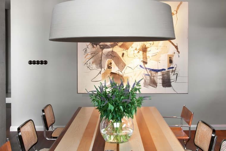 Oryginalny stół wykonany przez austriackiego stolarza artystę Johannesa Eckarta według pomysłu paryskiego projektanta mebli Thomasa Lemuta. Wokół niego krzesła klasyki Cesca chair Marcela Breuera (z 1928 r.) oraz włoskie krzesła vintage z lat 70. Nad blatem lampa Soho (Marset). W tle obraz 'Czarno-białe' Marzeny Jagiełło.