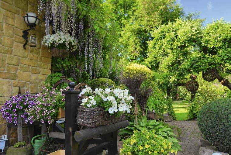 Zabytkowe sprzęty wyeksponowano w najbliższym otoczeniu domu - nawet koło młyńskie czy miotła zyskały pośród pięknych roślin status niemal dzieł sztuki.