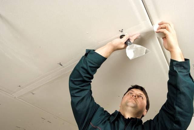 Montaż sufitu podwieszanego. Miejsca, w których płyty stykają się ze sobą, wzmacnia się taśmą papierową i szpachluje