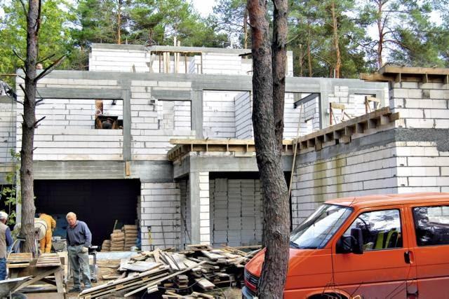 Ściany budynku wzniesiono z bloczków wapienno-piaskowych, następnie ocieplono od zewnątrz styropianem o grubości 15 cm i wykończono tynkiem akrylowym oraz drewnem
