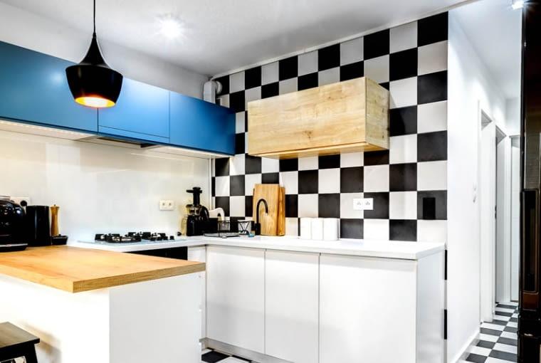 Kuchnia jest jasna i funkcjonalnie rozwiązana. Szachownicę z podłogi powtórzono tu także na ścianie.