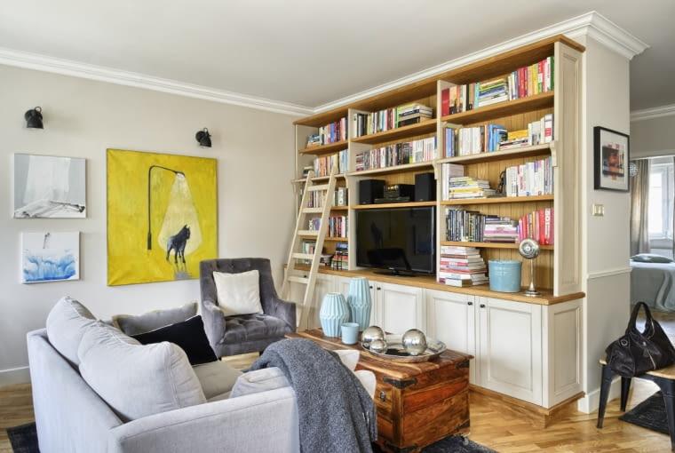 WREGALE znalazły swoje miejsce książki, przedtem porozrzucane po całym mieszkaniu. Drewniana skrzynia-schowek, pełniąca funkcję stolika kawowego, to jeden zpierwszych sprzętów kupionych przed laty do tego mieszkania. Żeby była bardziej mobilna, architekci postanowili przykręcić do niej kółka.