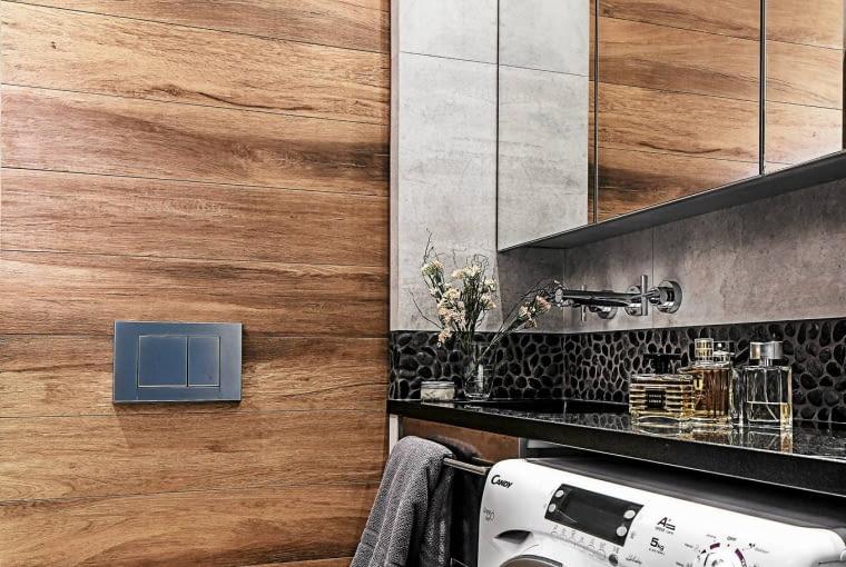 Mikroskopijna łazienka okazała się całkiem pojemna. Podgranitowym blatem zumywalką zmieściła się pralka ogłębokości 32cm. Wszafce z lustrzanymi drzwiczkami gospodarze przechowują kosmetyki izapasy środków czystości.