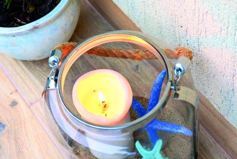 """Ten """"Morski"""" lampion jest zrobiony ze słoja, a jego rączka - ze sznurka. Piasek na dnie stabilizuje świecę."""