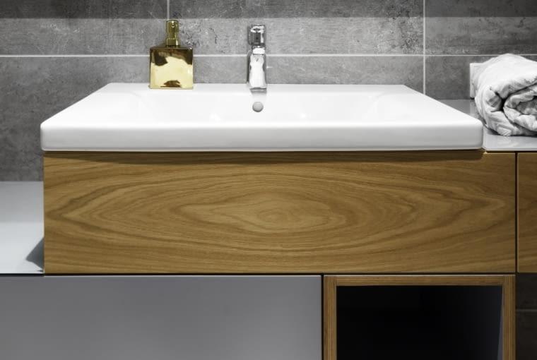 Szaro - biała łazienka z drewnianymi elementami.