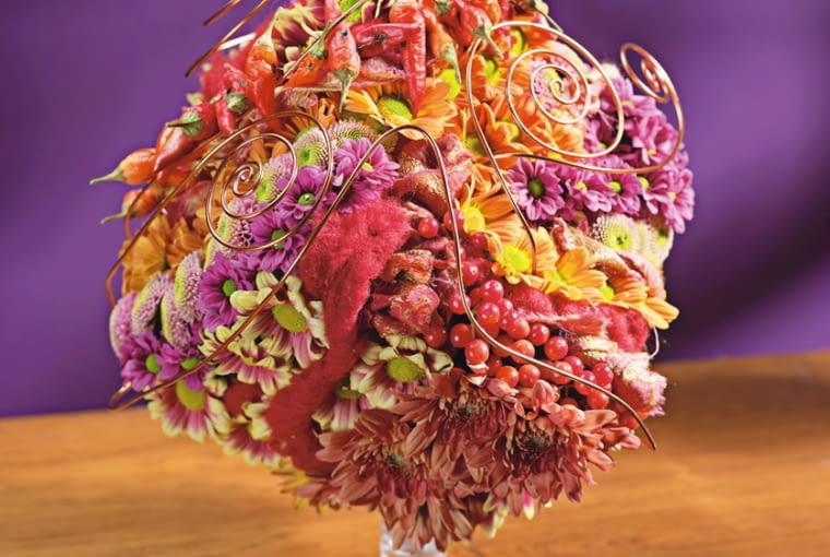 Orientalne kompozycje kwiatowe. Różne odmiany chryzantem gałązkowych zestawiono z papryczkami chili, kiśćmi kaliny koralowej i splotami czerwonej wełny. Całość ujęto w ażurową koronę z miedzianego drutu