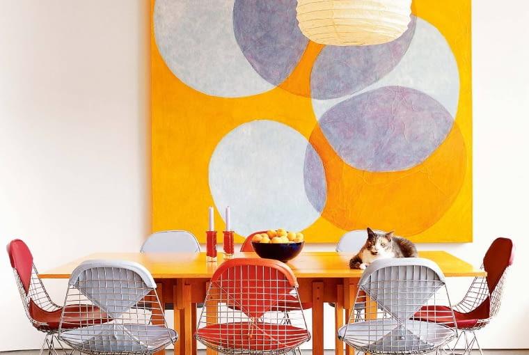 EKSPRESJA PONAD WSZYSTKO. Sugestywne kolory, odważne formy (druciane krzesła, rama stołu) i funkcjonalność (nowoczesna podłoga z żywicy epoksydowej) - przepis na udane wnętrze.