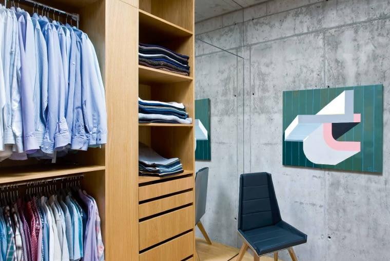 Nawet do garderoby dotarła sztuka - obraz autorstwa Marii Widelak. Surowość betonu to świetne tło dębowej zabudowy i wielobarwnych ubrań.