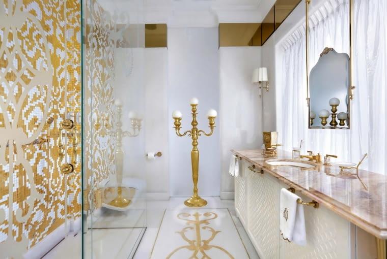 W pokoju kąpielowym przy małżeńskiej sypialni zachwyca dobór detali: stojący lichtarz, zawieszone na tle okna niezwykłe lustro Mayfair (Devon & Devon) i stylowe akcesoria. Uwagę przykuwa kunsztowny wzór, którym inkrustowana jest marmurowa posadzka, zaprojektowany przez Katarzynę Sybilską.