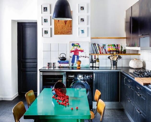 W kuchni jedyną plamą żywego koloru jest stół, a mimo to wnętrze emanuje radosną energią. Lampy Caravaggio (proj. Cecilie Manz), krzesła z wyprzedaży. Drzwi Sarah pomalowała farbą Czarna Rzodkiew z własnej kolekcji.