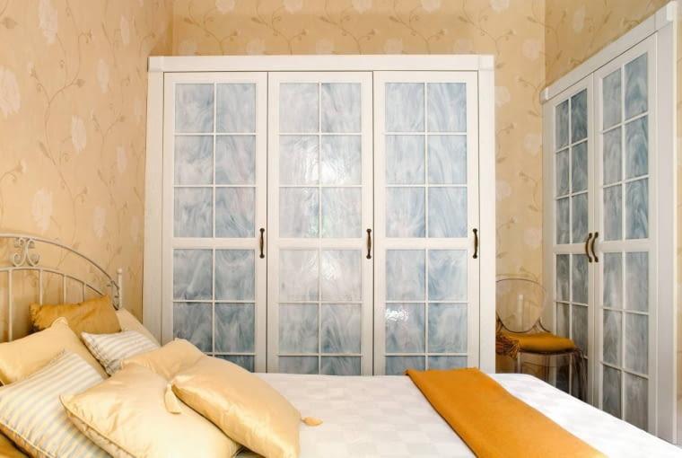 W sypialni udałosię zmieścić dwie pojemne szafy:wolno stojącą orazwbudowaną wewnękę. Obie zostały zrobione nawymiar zrozbielonego drewna jesionu.